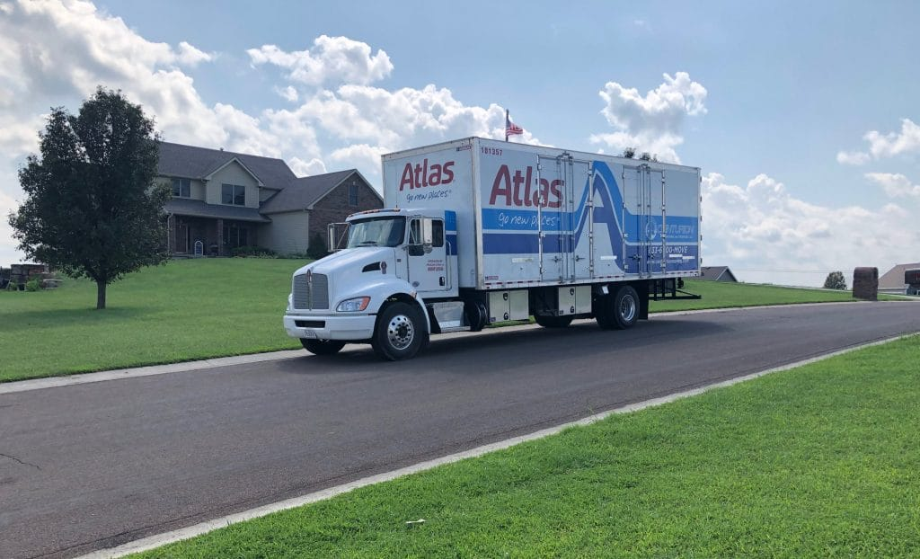 Centurion Moving & Storage moving truck co-branded with Atlas Vanlines in front of Overland Park, KS home